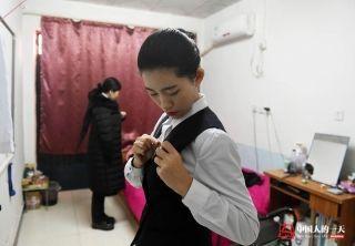 晓培整理自己的服饰,戴上接机员徽章。 (来自:腾讯图片) (摄影:张伟)