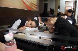 中午吃过饭后,大家趁着航班到达的间隙,趴在桌上打个盹。 (来自:腾讯图片) (摄影:张伟)