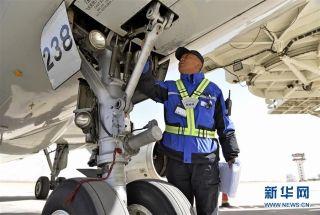 民航西藏区局机务工程部机械师普登对飞机起落架进行检查(2月25日摄)。 (摄影:刘东君)