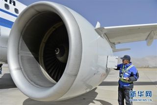 民航西藏区局机务工程部机械师普登在检查飞机发动机滑油量(2月25日摄)。 (摄影:刘东君)