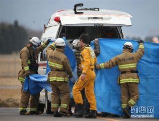 3月6日,在日本长野县松本市,消防员转移遇难者遗体。