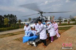 图为医护人员接病人下飞机。中新社记者 任东 摄