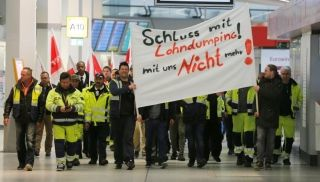 Members of Germany's Verdi union take part in a warning strike by ground services, security inspection and check-in staff at Tegel airport in Berlin, Germany March 10, 2017. The placard reads 'Enough with our wage cuts'. REUTERS/Hannibal Hanschke