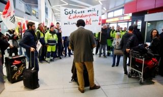 A passenger blocks the way of a demonstration of members of Germany's Verdi union during a warning strike by ground services, security inspection and check-in staff at Tegel airport in Berlin, Germany March 10, 2017. REUTERS/Hannibal Hanschke