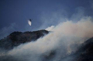 村民上坟引山火 直升机浓烟中紧急灭火