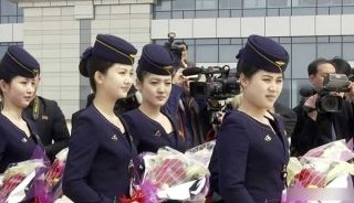 Air Koryo crew members wait for Chinese passengers with bouquets. [Photo/Xinhua]
