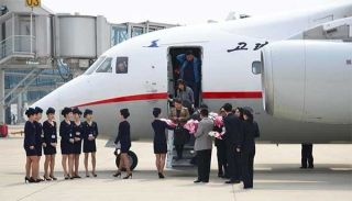 Air Koryo crew members present bouquets to passengers at the Pyongyang Sunan International Airport on March 28. [Photo/Xinhua]