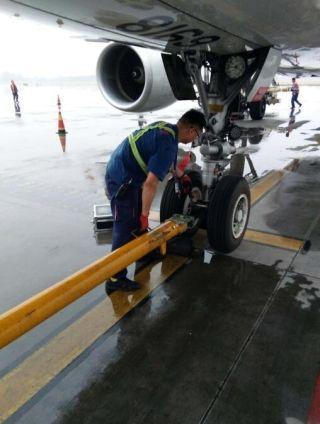 机务员在雨中保障航班起降。周蕾摄