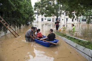 图为在洪水中艰难行动的村民。