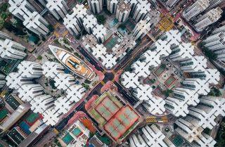 香港九龙,曾经是世界人口密度最高的地方,90年代大拆迁,旧城改造,建筑向空中延伸,摄影师航拍这些密集的建筑物,这种封闭的蜗居,窗户是人们接触外界空气的唯一途径。