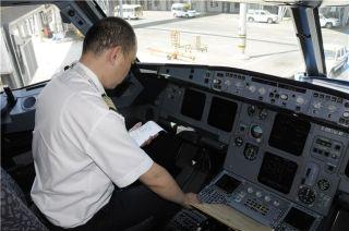 飞机驾驶舱内,机长正在认真核对每项数据。