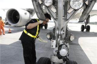 机务保障人员正在检查前起落架。