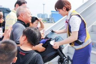 7月13日下午,杭州萧山国际机场机坪实时温度高达54℃,为了加快旅客登机速度,防止旅客在烈日高温下产生不适,厦航乘机员何梦凡主动俯下身子帮旅客折叠婴儿车。(刘晓虹 摄)