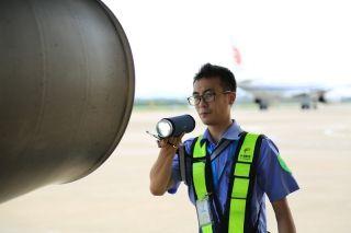 发动机尾喷处高达200°的高温,维修人员迎着热风睁不开眼。