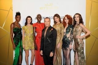 Julien Macdonald poses with models wearing his iconic designs at the launch of Etihad Airways' promotional fashion film 'Runway to Runway' at NYFW: The Shows in New York City
