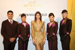 Model Montana Cox poses with Etihad Airways Cabin Crew at the launch of Etihad Airways' promotional fashion film 'Runway To Runway' at NYFW: The Shows in New York City