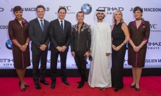 (L-R) Patrick Pierce, Etihad Airways Vice President Marketing Partnerships, Peter Baumgartner, Etihad Airways Chief Executive Officer, Designer Julien Macdonald OBE, Mohammad Al Balooki, Etihad Airways Executive Vice President Commercial, Linda Celestino, and Etihad Airways Vice President Guest Experience Delivery flanked by members of Etihad Airways' Cabin Crew