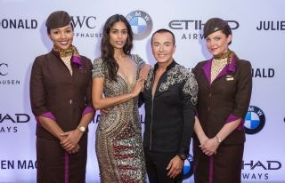 (L-R) A member of Etihad Airways' Cabin Crew, a model wearing a Julien Macdonald outfit, Julien Macdonald and a member of Etihad Airways' Cabin Crew