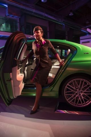 An Etihad Airways Cabin Crew gets out of a BMW 760iL on display at the Etihad Airways Innovation Academy