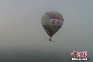 图为石春艳从热气球上跳下。