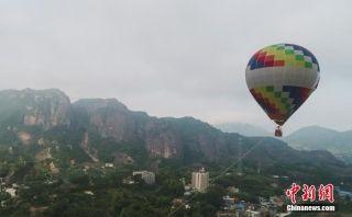图为热气球升致丹霞地貌上空。