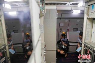 9月29日晚上22时18分和23时19分,东航2架A330-300宽体飞机从上海浦东机场起飞,飞往加勒比海岛国安提瓜和巴布达的维尔·伯德机场,将在那里把从多米尼克转移的中方人员紧急接运回国。图为乘务员们正在飞机客舱内做着起飞前的准备。中新社记者 殷立勤 摄