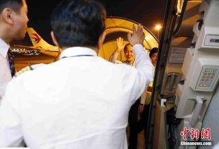 9月29日晚上22时18分和23时19分,东航2架A330-300宽体飞机从上海浦东机场起飞,飞往加勒比海岛国安提瓜和巴布达的维尔·伯德机场,将在那里把从多米尼克转移的中方人员紧急接运回国。图为东航机长与地面工作人员挥手告别。中新社记者 殷立勤 摄