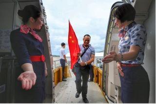"""""""欢迎回家!""""东航乘务员们站在机舱门口热烈欢迎登机的受困同胞。(来源:人民日报客户端 摄影:人民网 王初摄)"""