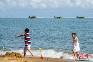 小朋友在海口湾沙滩玩耍,在他们身后三架赛斯纳208B-EX型水陆两用飞机正在进行低空飞行表演。