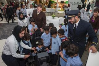 Delighted children try out their skills on a flight simulator at Etihad Airways' stand during the WorldSkills Abu Dhabi 2017 event in the UAE's capital city