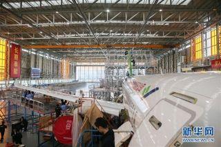 工作人员在中国商飞公司上海飞机制造有限公司总装车间内对C919大型客机102架机进行系统装配 摄影:新华社记者 丁汀