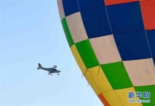 11月11日,一架固定翼飞机在活动现场从热气球旁飞过。 摄影:新华社记者岳月伟