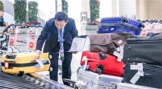2月13日,春运中转行李数量高达777件,行李员刘帅鹏正在仔细辨认行李牌上的目的地信息,对行李进行分类,方便后续中转。 (摄影:朱国涛)