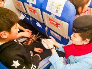 2月20日,MF8114北京至泉州航班,乘务员发现有名儿童鼻子出血,马上拿了些纸巾给其擦拭,并准备冰块和湿毛巾给小朋友冰敷。 (摄影:赵沫)