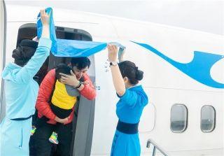 2月22日,MF8386广州—泉州航班落地后停靠客梯车,泉州小雨,考虑到航班中有很多儿童旅客,乘务组在客舱门口撑起袋子,为旅客遮风挡雨。 (摄影:王媛媛)