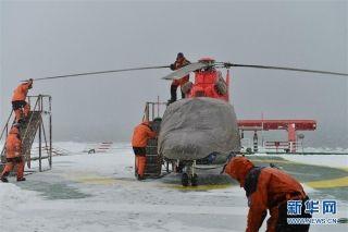 中国第34次南极科考队直升机机组人员在风雪中进行检查作业,为飞行任务做准备(1月18日摄)。