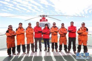 """在""""雪龙""""船飞行甲板的""""海豚""""直升机前,完成了南极中山站卸货运输任务的中国第34次南极科考队直升机机组成员合影(1月4日摄)。"""