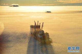 """这是完成中山站卸货任务的直升机机长杨佃良驾驶直升机返航时拍摄的在雾气缭绕的南极海冰中的""""雪龙""""船(1月3日摄)。"""