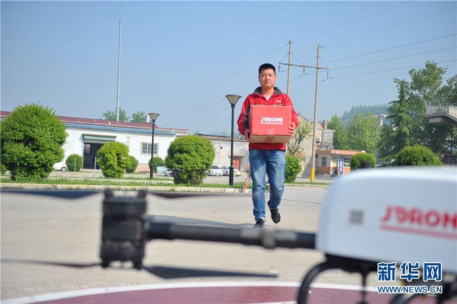京东配送员正将快递搬往无人机。摄影:王智超