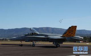 """5月6日,澳大利亚皇家空军RAAP飞行表演队在""""伊拉瓦拉之翼""""航展上飞过停在机场上的F/A-18大黄蜂战机。新华网记者 白雪飞 摄"""