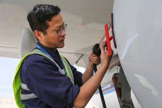 """维修人员将水洗管路连接到发动机上。图解飞机发动机""""洗澡""""。 (摄影:罗伟)"""