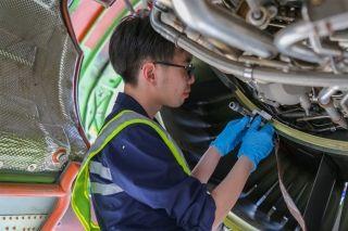 """维修人员在发动机上固定管路。图解飞机发动机""""洗澡""""。 (摄影:罗伟)"""