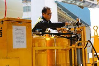 """维修人员将水洗溶液注入设备进行调试。图解飞机发动机""""洗澡"""" (摄影:罗伟)"""