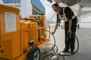 """维修人员将发动机上的管路与水洗设备连接。图解飞机发动机""""洗澡"""" (摄影:罗伟)"""