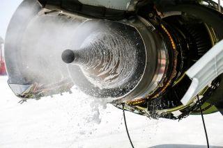 """水洗溶液在发动机内经过浸泡后冷转喷出。图解飞机发动机""""洗澡"""" (摄影:张洁)"""