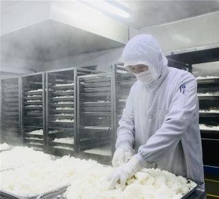 刚出锅近100℃的米饭,厨师要用手翻松。