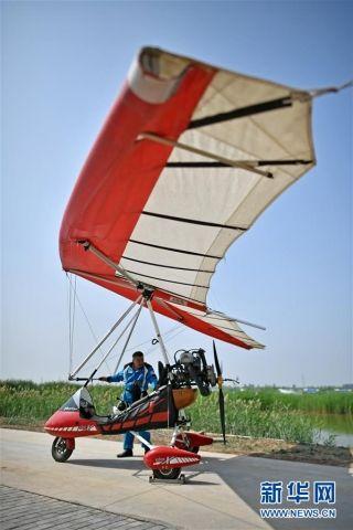 刘亦兵在飞行前对动力三角翼飞机进行检查。摄影: 王鹏