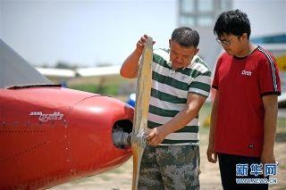 刘亦兵(左)在飞行营地与儿子交流飞机技术知识。摄影:王鹏
