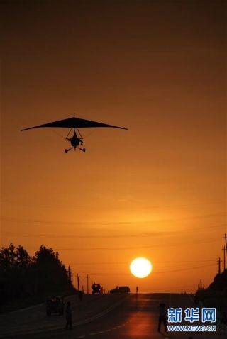 刘亦兵在日出时驾驶动力三角翼飞机执行航拍飞行任务(资料照片)。