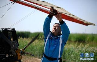 刘亦兵在飞行前对动力三角翼飞机进行检查。摄影:王鹏